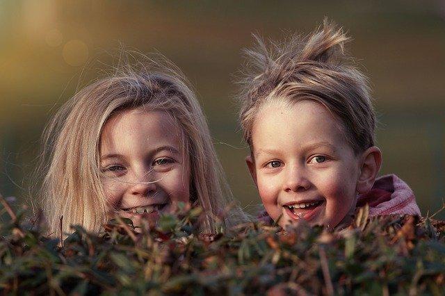 smějící se děti za keřem