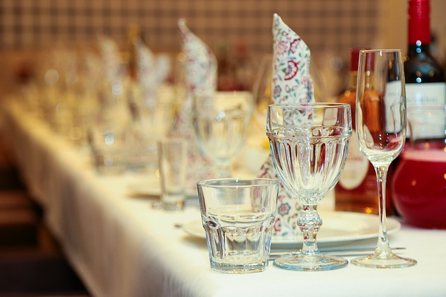 prostřený dlouhý stůl, nachystané sklenice, ubrousky